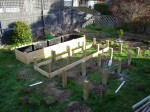 Raised Bed #3 has all its posts set. You can see the slats being built for Raised Bed #2